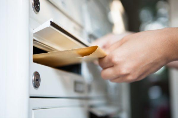 Frau, die Brief in Briefkasten einwirft
