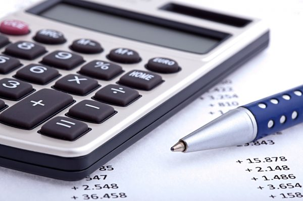 Taschenrechner und Kuli auf Blatt mit Kalkulationen