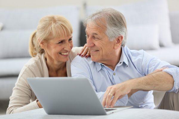 Ehepaar am Laptop vor Sofa